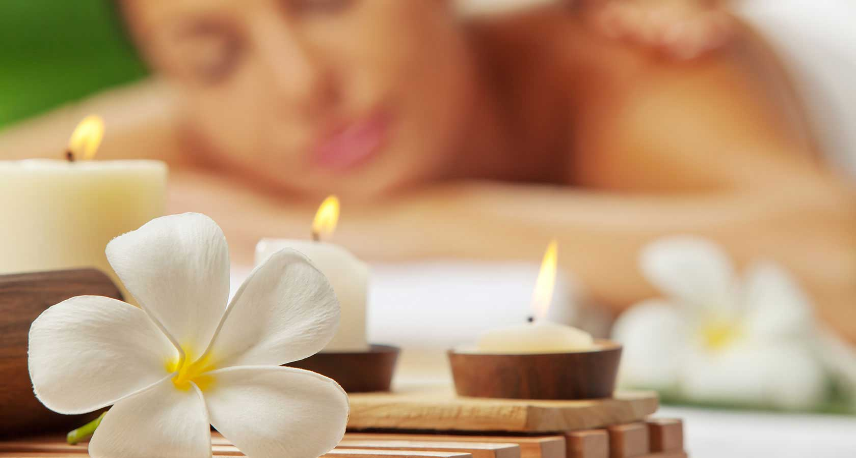 White flower, candles and woman enjoying spa treatment out of focus in background